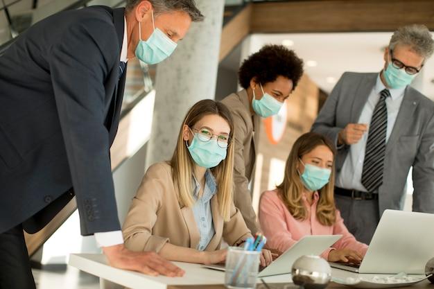 Eine gruppe von geschäftsleuten trifft sich und arbeitet im büro und trägt masken zum schutz vor dem koronavirus