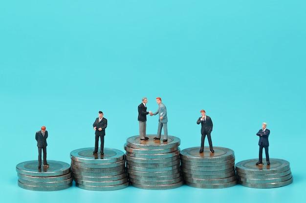 Eine gruppe von geschäftsmann steht auf münze stapeln podium