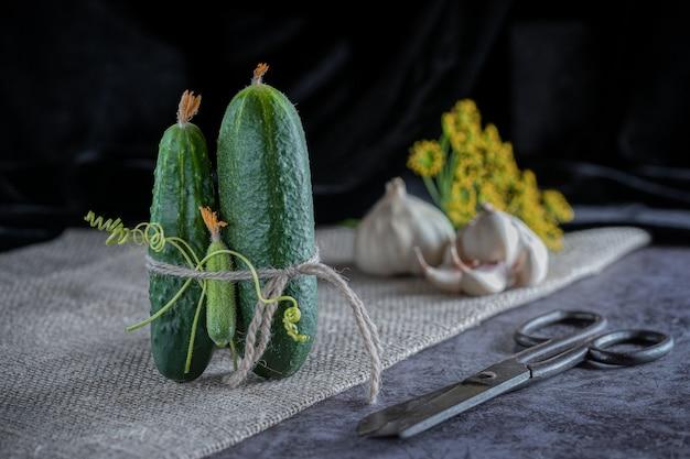 Eine gruppe von gurken auf dem tisch mit indrigentov zum salzen: knoblauch, dill. dunkler hintergrund.
