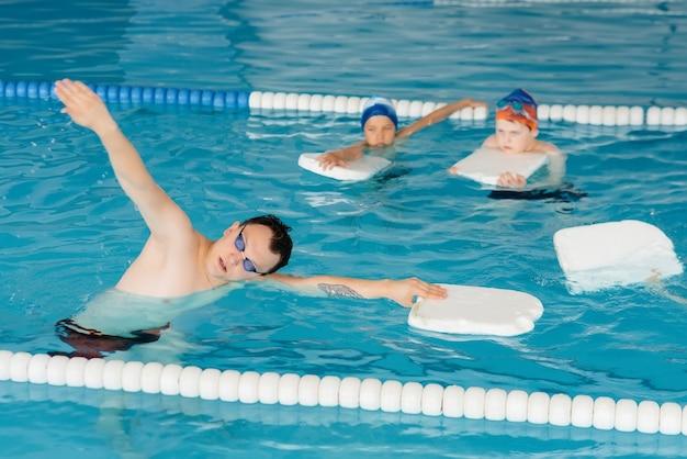 Eine gruppe von jungen und mädchen trainiert und lernt mit einem lehrer das schwimmen im pool. entwicklung des kindersports. Premium Fotos