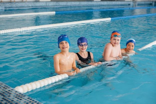Eine gruppe von jungen und mädchen trainiert und lernt mit einem lehrer das schwimmen im pool. entwicklung des kindersports.