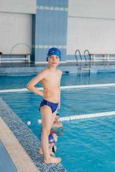 Eine gruppe von jungen und mädchen trainiert und lernt mit einem lehrer das schwimmen im pool