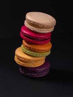 Eine gruppe von keksen, die als macarons auf einem schwarzen tisch bekannt sind. kleine runde süße kekse mit füllung.