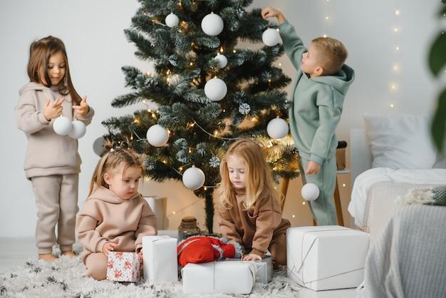 Eine gruppe von kindern gibt ihrem freund am weihnachtsmorgen geschenke, die auf dem boden im wohnzimmer vor dem hintergrund von weihnachtsbäumen sitzen. konzept des austauschs von geschenken für weihnachten.
