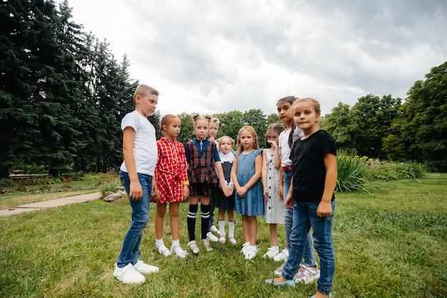 Eine gruppe von kindern läuft herum, hat spaß und spielt im sommer als größeres team im park. glückliche kindheit.