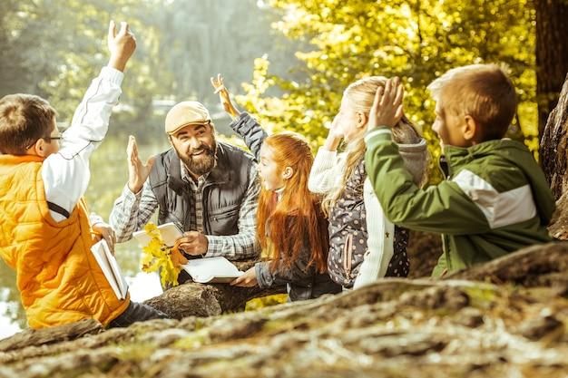 Eine gruppe von kindern mit erhobenen händen, die an einem guten tag unterricht bei einem lehrer im wald haben