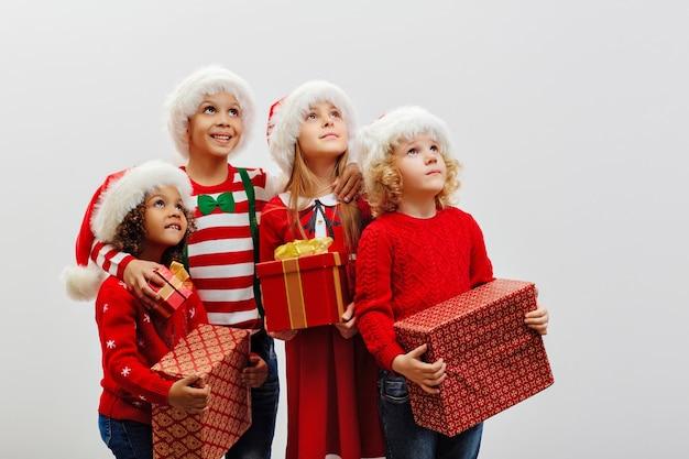 Eine gruppe von kindern mit weihnachtsgeschenken in den händen in festtagskostümen schaut interessiert auf