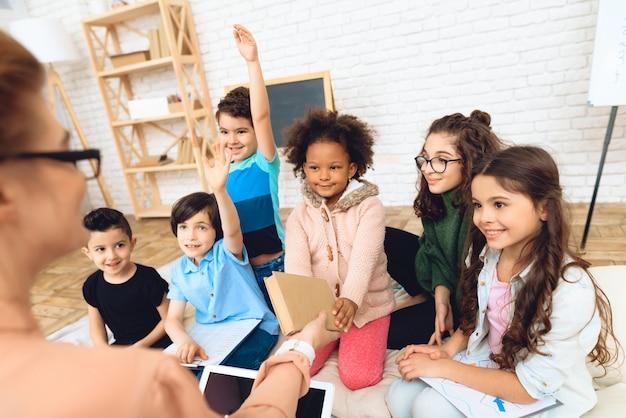 Eine gruppe von kindern zieht an den händen, um die frage des lehrers in der grundschule zu beantworten.
