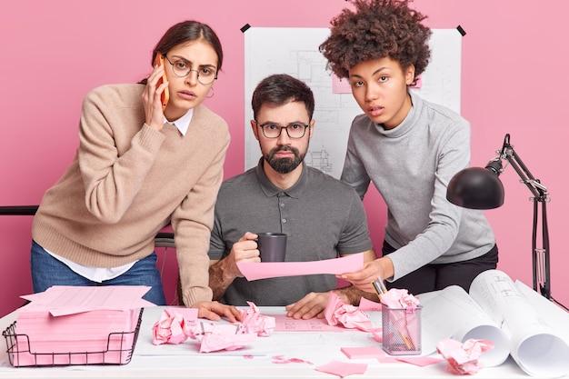 Eine gruppe von kollegen diskutiert ideen für ein startup-projekt erstellen sie eine neue architektenskizze zusammen copperate, um die gemeinsame aufgabe zu beenden, umgeben von papieren, die in der nähe des desktops posieren, diskutieren ideen. brainstorming-konzept