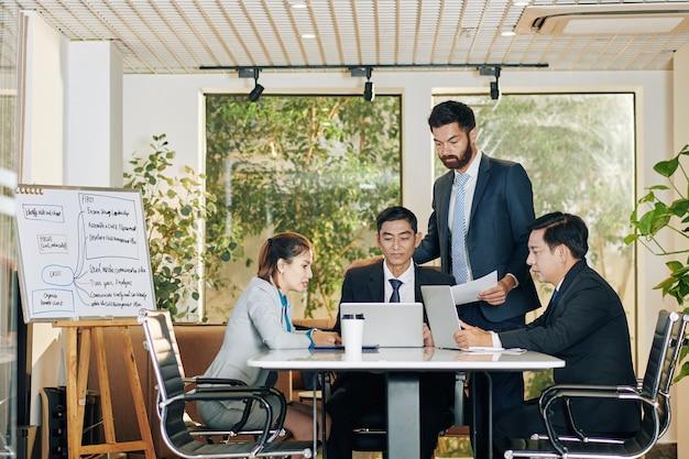Eine gruppe von kollegen versammelte sich am tisch im besprechungsraum, um die arbeitsergebnisse zu besprechen