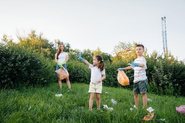 Eine gruppe von mädchen mit kindern bei sonnenuntergang beschäftigt sich mit der müllabfuhr im park. umweltschutz, recycling.