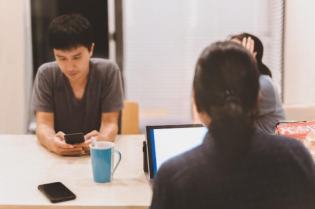 Eine gruppe von menschen arbeitet spät in der nacht am küchentisch und arbeitet am laptop