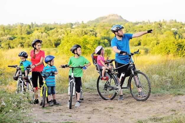 Eine gruppe von menschen auf fahrrädern - zwei erwachsene und vier kleine kinder in fahrradausrüstung und helmen gegen die oberfläche von bäumen, park und grünem gras