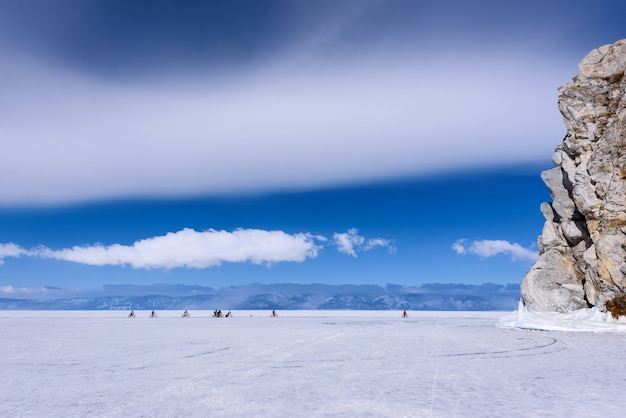 Eine gruppe von menschen fährt fahrrad auf dem zugefrorenen baikalsee nahe kap burkhan bei sonnigem wetter mit schönem wolkenhimmel