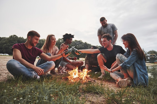 Eine gruppe von menschen hat ein picknick am strand. freunde haben spaß am wochenende.