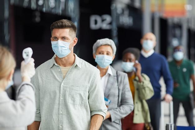 Eine gruppe von menschen in schutzmasken wird im freien auf der straße getestet