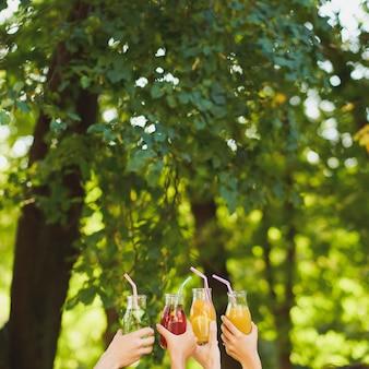 Eine gruppe von menschen jubelt mit detox-saft-cocktails auf grüner natur