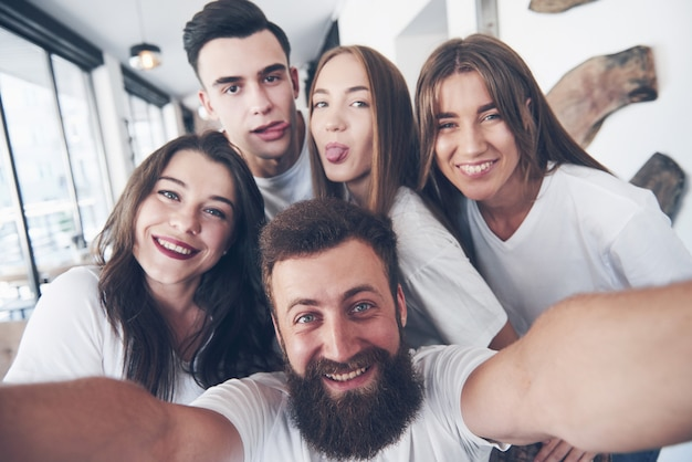 Eine gruppe von menschen macht ein selfie-foto in einem café. die besten freunde versammelten sich an einem esstisch, aßen pizza und sangen verschiedene getränke