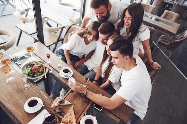Eine gruppe von menschen macht ein selfie-foto in einem café. die besten freunde versammelten sich an einem esstisch, aßen pizza und sangen verschiedene getränke.
