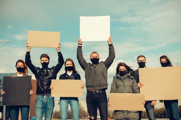 Eine gruppe von menschen mit maske und plakaten zum protest der protest der bevölkerung gegen das coronavirus und gegen die einführung der quarantäne