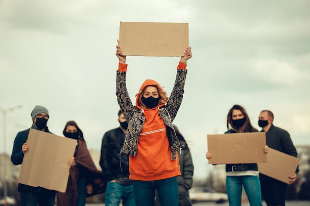 Eine gruppe von menschen mit maske und plakaten zum protest der protest der bevölkerung gegen das coronavirus