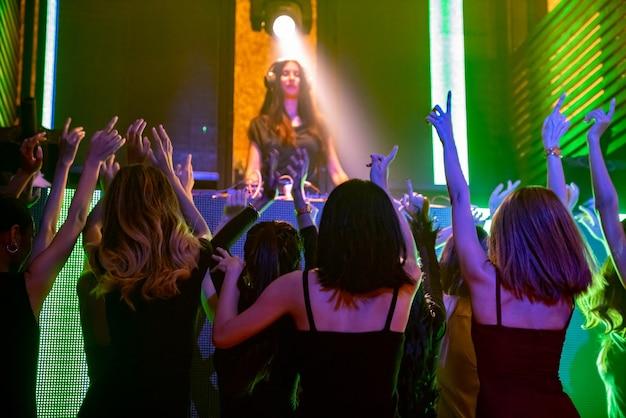 Eine gruppe von menschen tanzt im disco-nachtclub im rhythmus der musik von dj auf der bühne