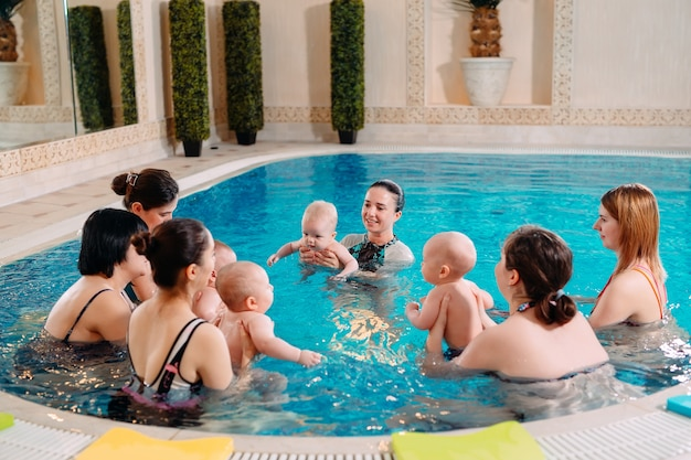 Eine gruppe von müttern mit ihren kleinen kindern in einem kinderschwimmkurs mit einem trainer.