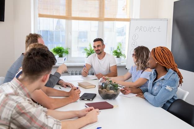 Eine gruppe von personen bei einem geschäftstraining hört dem sprecher zu. teamarbeit in einem internationalen unternehmen