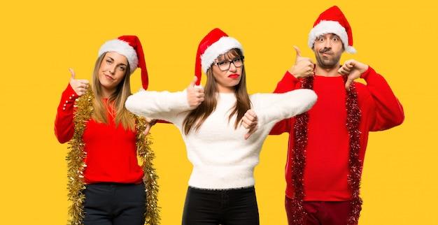 Eine gruppe von personen blonde frau kleidete oben für die weihnachtsfeiertage an, die gut-schlechtes zeichen bilden