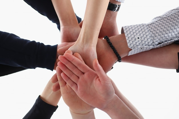 Eine gruppe von personen in anzügen kreuzte die hände im stapel, um zu gewinnen