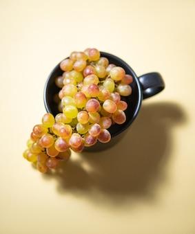 Eine gruppe von saftigen grün-rosa trauben in einem schwarzen becher