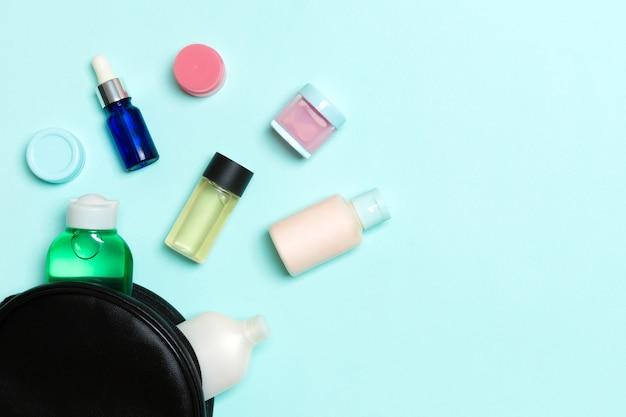 Eine gruppe von schönheitscremeflaschen fiel aus dem kosmetikbeutel auf blauem hintergrund heraus. platz für ihr design. draufsicht des hautpflegekonzepts