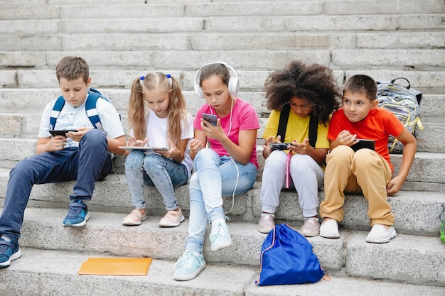 Eine gruppe von schulkindern in bunten kleidern sitzt auf den stufen und schaut sich geräte an. fünf klassenkameraden verschiedener nationalitäten.