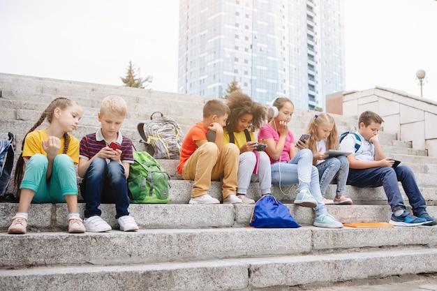 Eine gruppe von schulkindern in bunten kleidern sitzt auf den stufen und schaut sich geräte an. sieben klassenkameraden verschiedener nationalitäten.
