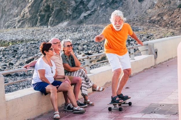 Eine gruppe von senioren und reifen menschen am strand hat spaß daran, einen alten mann zu betrachten, der ein skateboard fährt und mit angstgesicht lacht - frau, die den mann berührt