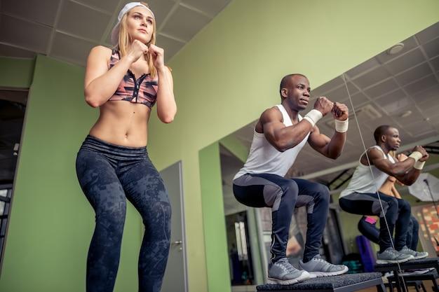 Eine gruppe von sportlern springt in einem cross-training-fitnessstudio über einige boxen