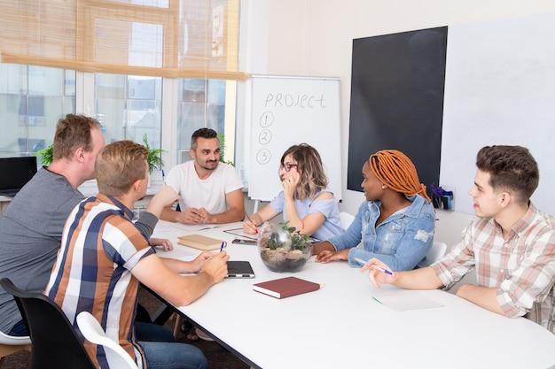 Eine gruppe von studenten bei einem geschäftstraining hört dem sprecher zu.
