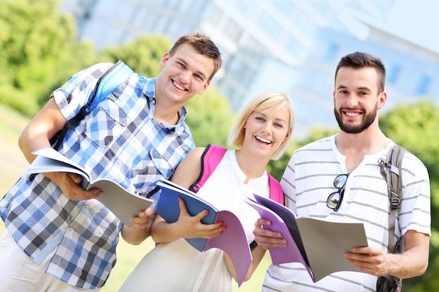 Eine gruppe von studenten, die im park vor modernen gebäuden stehen