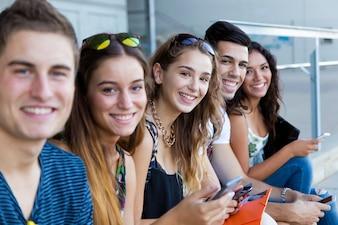 Eine Gruppe von Studenten, die Spaß mit Smartphones nach dem Unterricht haben.