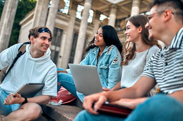 Eine gruppe von studenten mit laptops sitzt auf den stufen in der nähe des campus und kommuniziert.