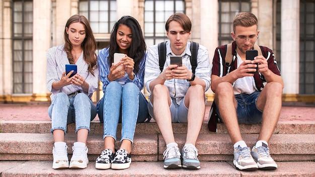 Eine gruppe von studenten sitzt auf den stufen vor dem campus und benutzt ihre smartphones