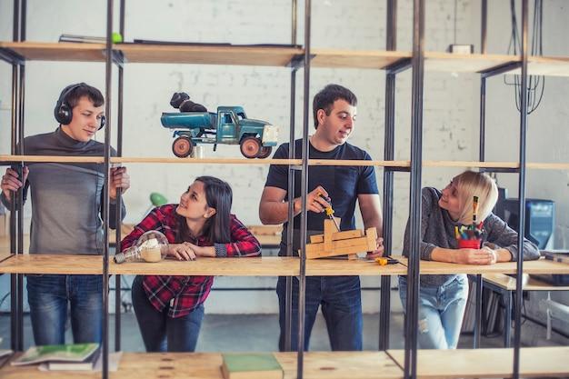 Eine gruppe von studentenfreunden macht und diskutiert kreative ideen auf dem dachboden