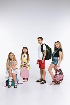 Eine gruppe von süßen und entzückenden teenagern oder schülern ist wieder in der schule. über weißem studiohintergrund. das konzept freundschaft, bildung, kindheit, kindermode