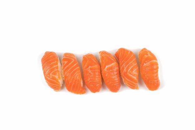 Eine gruppe von sushi-lachs in der reihe. dies ist das traditionelle japanische essen, das zwischen rohem frischem lachs und reis gegessen wird.