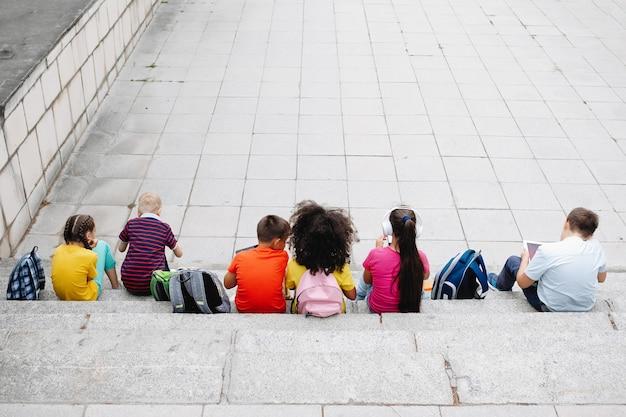 Eine gruppe von teenagern in bunten kleidern sitzt auf den stufen. sieben klassenkameraden, rückansicht.