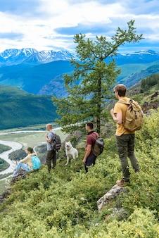Eine gruppe von touristen, die mit rucksäcken und einem hund auf dem gipfel des berges befreundet sind, genießen die aussicht auf die berge