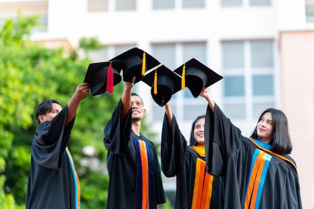 Eine gruppe von universitätsabsolventen setzte einen schwarzen hut auf und gratulierte ihnen zum abschlusstag.