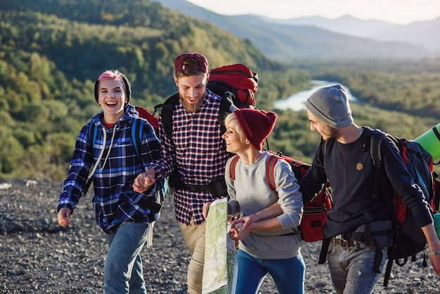 Eine gruppe von vier glücklichen reisenden geht mit der karte spazieren
