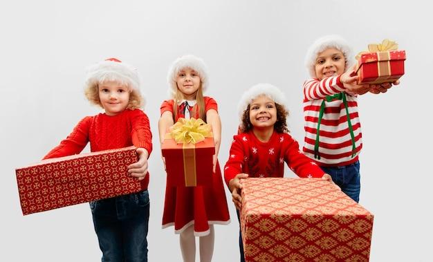 Eine gruppe von vier kindern mit weihnachtsgeschenken in den händen in weihnachtskostümen