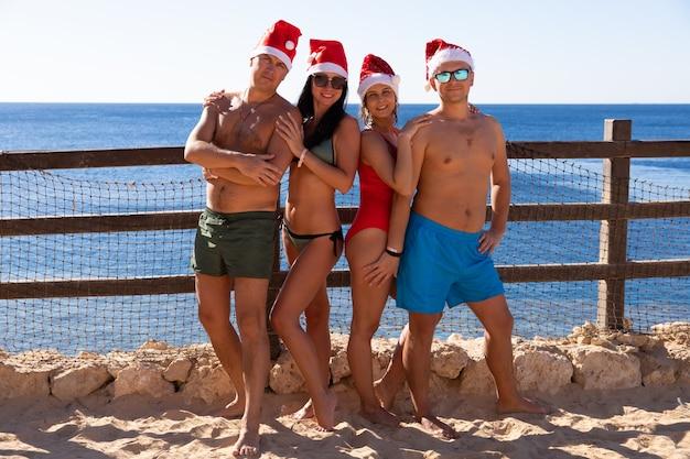 Eine gruppe von vier personen in badebekleidung und roten weihnachtsmützen feiert weihnachten